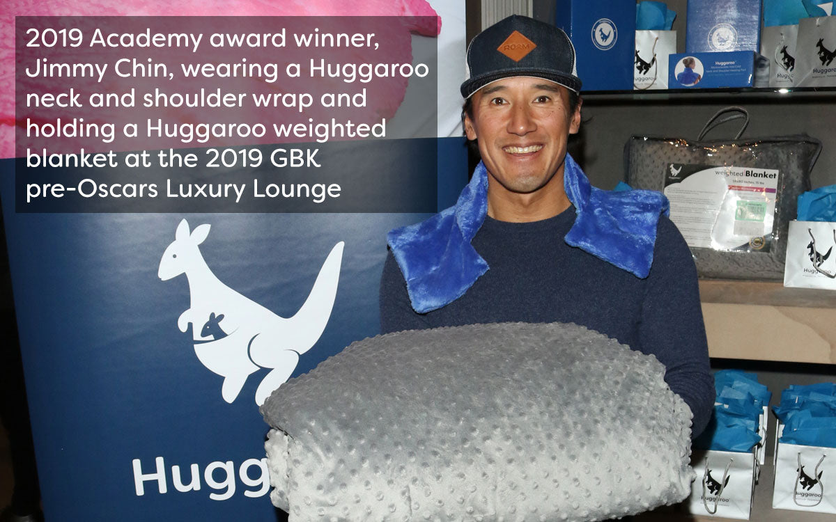academy award winner jimmy chin wearing a huggaroo wrap and holding a huggaroo weighted blanket
