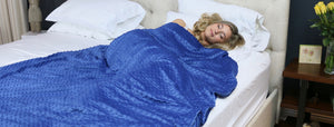 Young woman sleeping under a blue Huggaroo weighted blanket