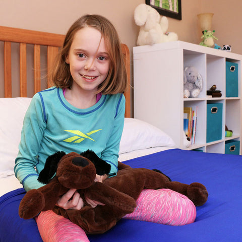 girl with a puppy huggaroo weighted lap pad on her lap