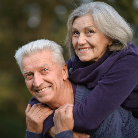 a happy elderly couple hugging