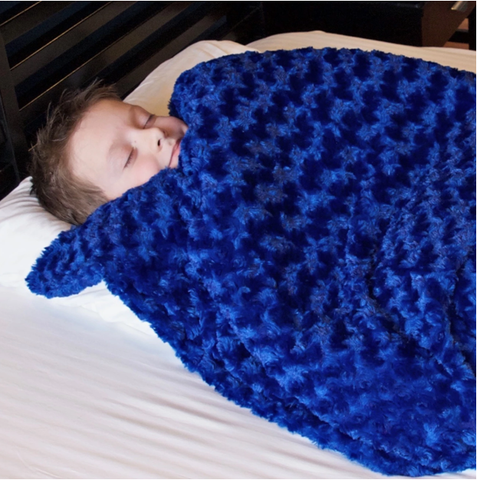 boy snuggled under his blue chenille 7 lb huggaroo weighted blanket