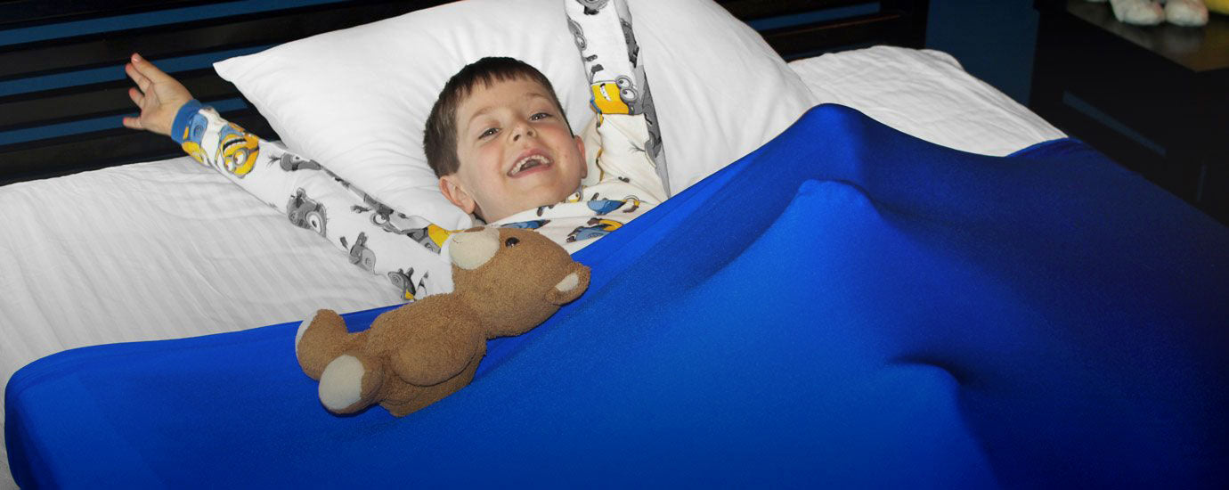 a young boy smiling and relaxing under his huggaroo pouch sensory compression bed sheet