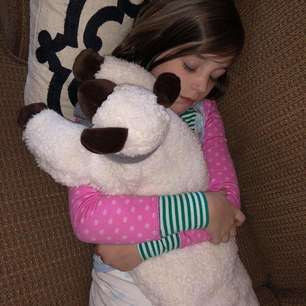young girl hugging her huggaroo lamb weighted lap pad
