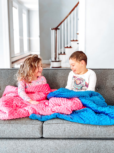 a boy and a girl with their huggaroo 7 lb weighted blankets
