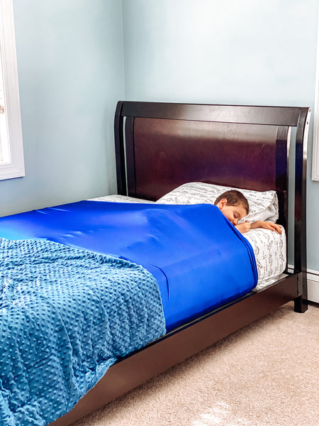 young boy asleep under his huggaroo Pouch sensory compression bed sheet