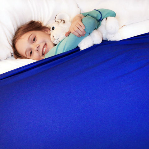 girl smiling under her huggaroo pouch sensory compression bed sheet