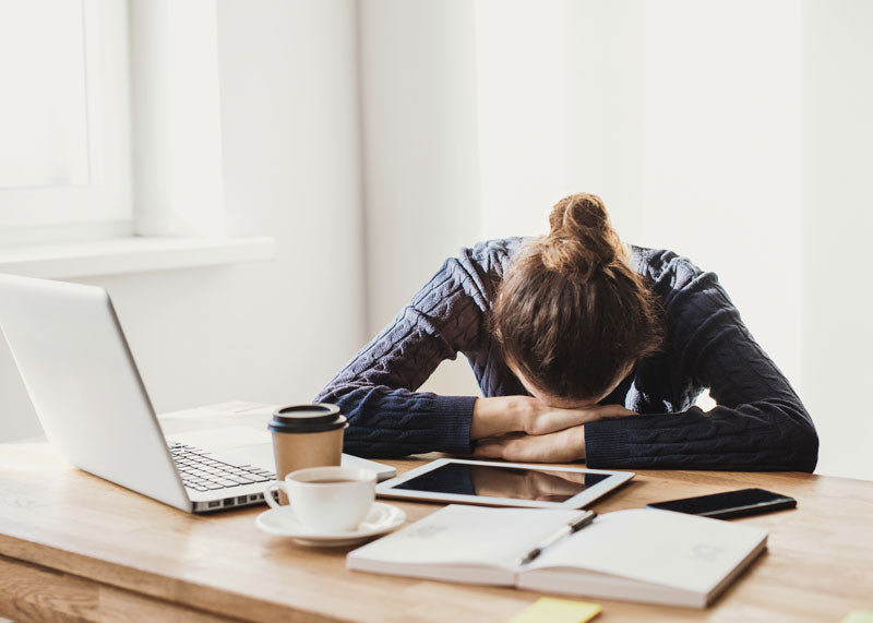 Stressed student resting head in hands