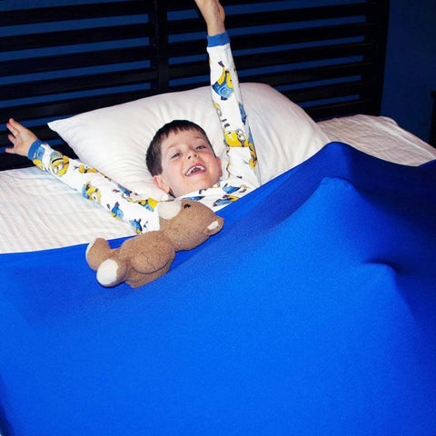 cute boy playing under his Huggaroo Pouch sensory bedsheet