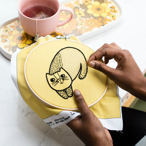 Person stitching cat hoop