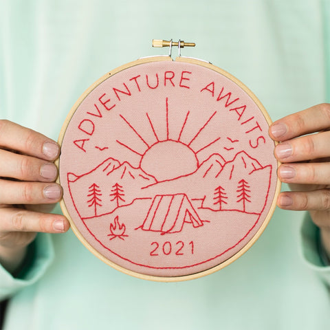 Pink with red thread Adventure Awaits hoop being held by a woman wearing a mint green jumper