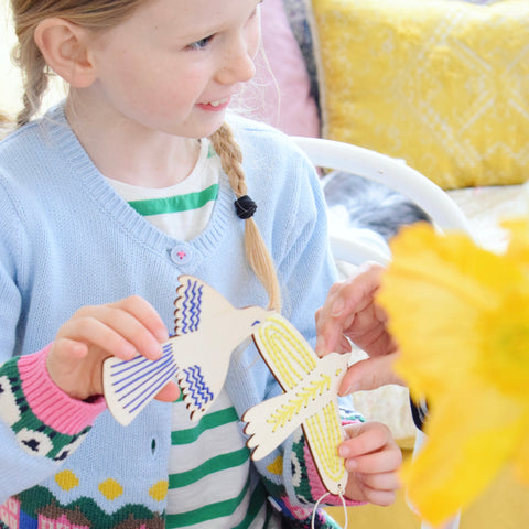 Young girl holding colourful embroidered wooden birds