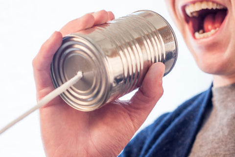 man smiling while talking into a can to contact the open box