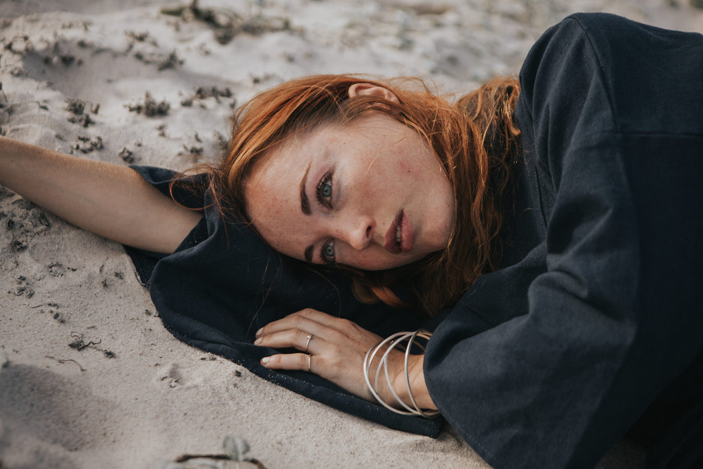 Woman lying on beach wearing recycled silver bangle and  fairtrade gold and silver ecofriendly rings