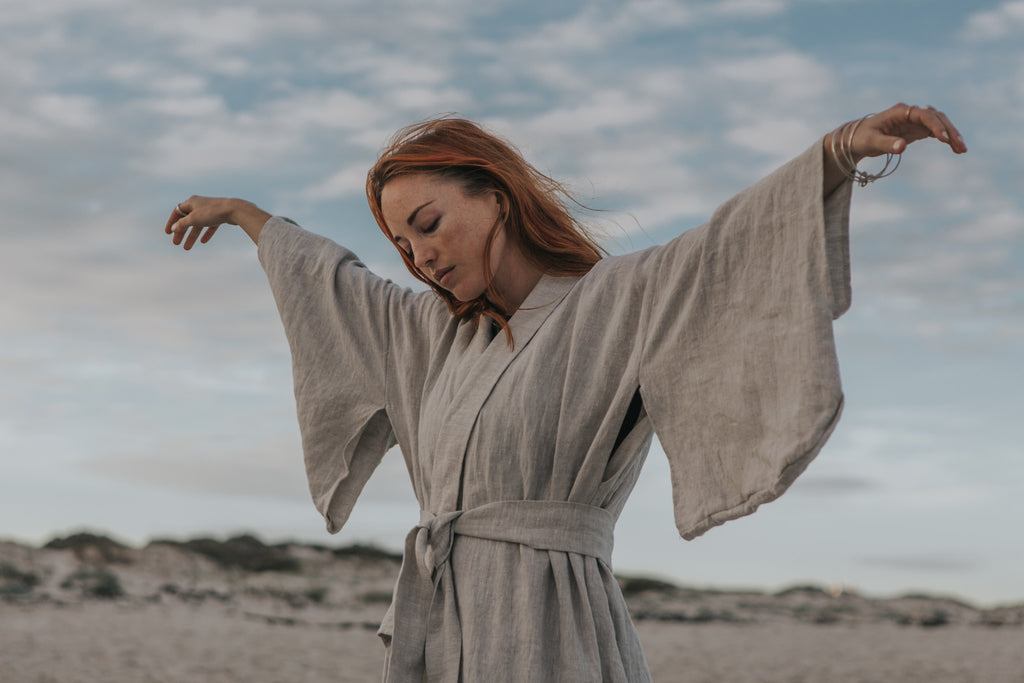 A moment of quite reflection wearing a linen wrap dress and sustainable, ecofriendly jewellery