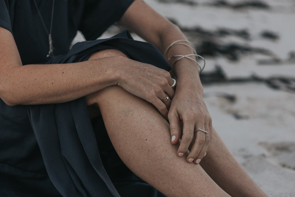 Quiet time on the seashore, woman wearing minimalist handcrafted jewellery and ecofriendly dress