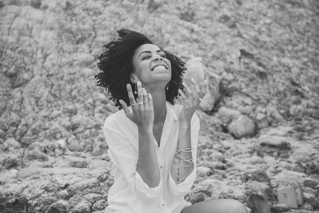 A woman laughs whilst wearing ethical, ecofriendly jewellery