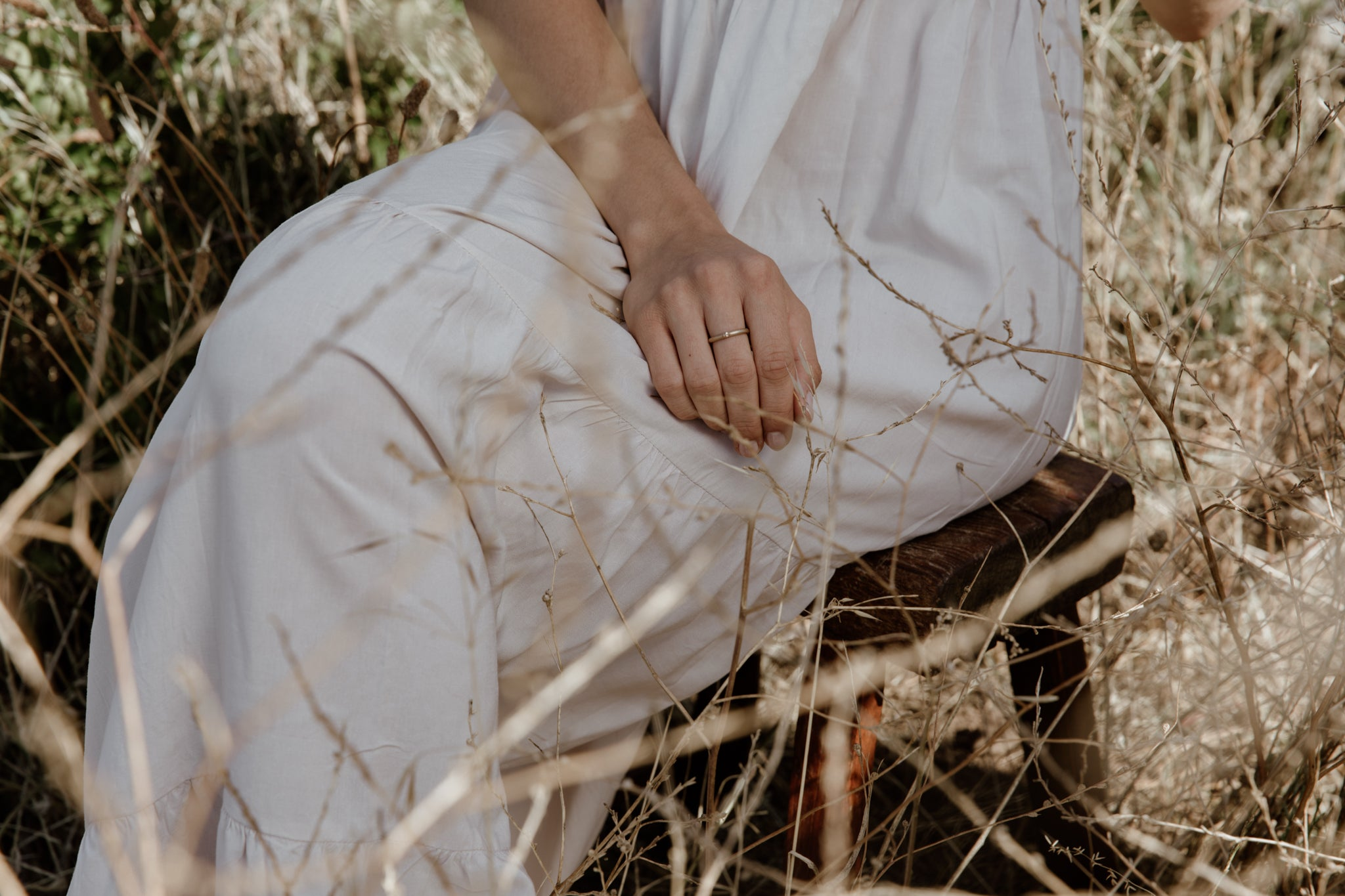 Woman in white linen dress wearing dainty recycled gold ring