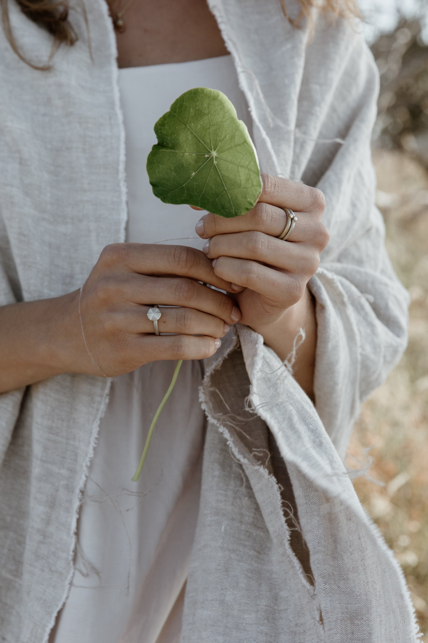 Ethical, recycled silver and gold rings worn with natural linen slowfashion dress and shawl