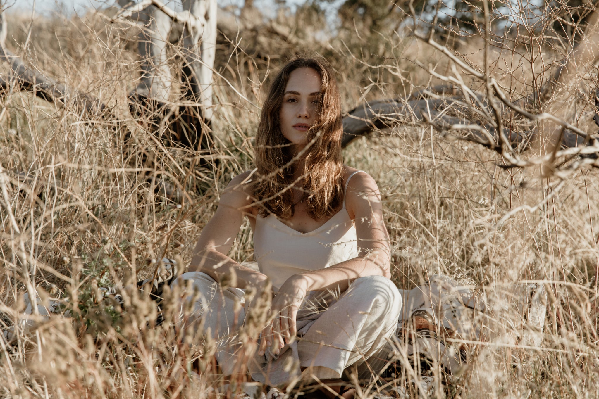 Quiet moments in nature, woman wearing slow fashion linen dress and sustainable rings, necklace and earrings