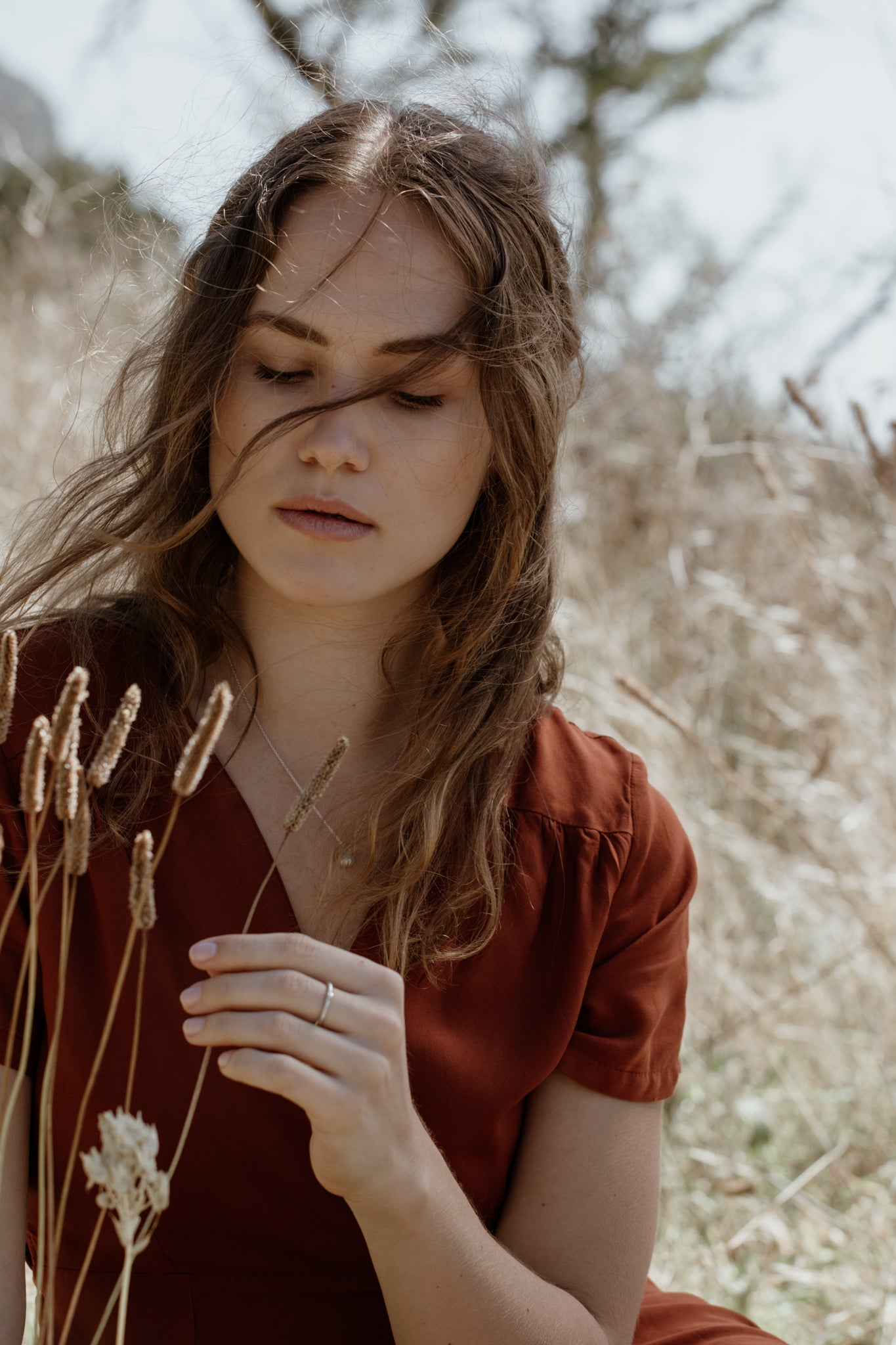Woman in slow fashion dress in nature with sustainable, ecofriendly jewelry