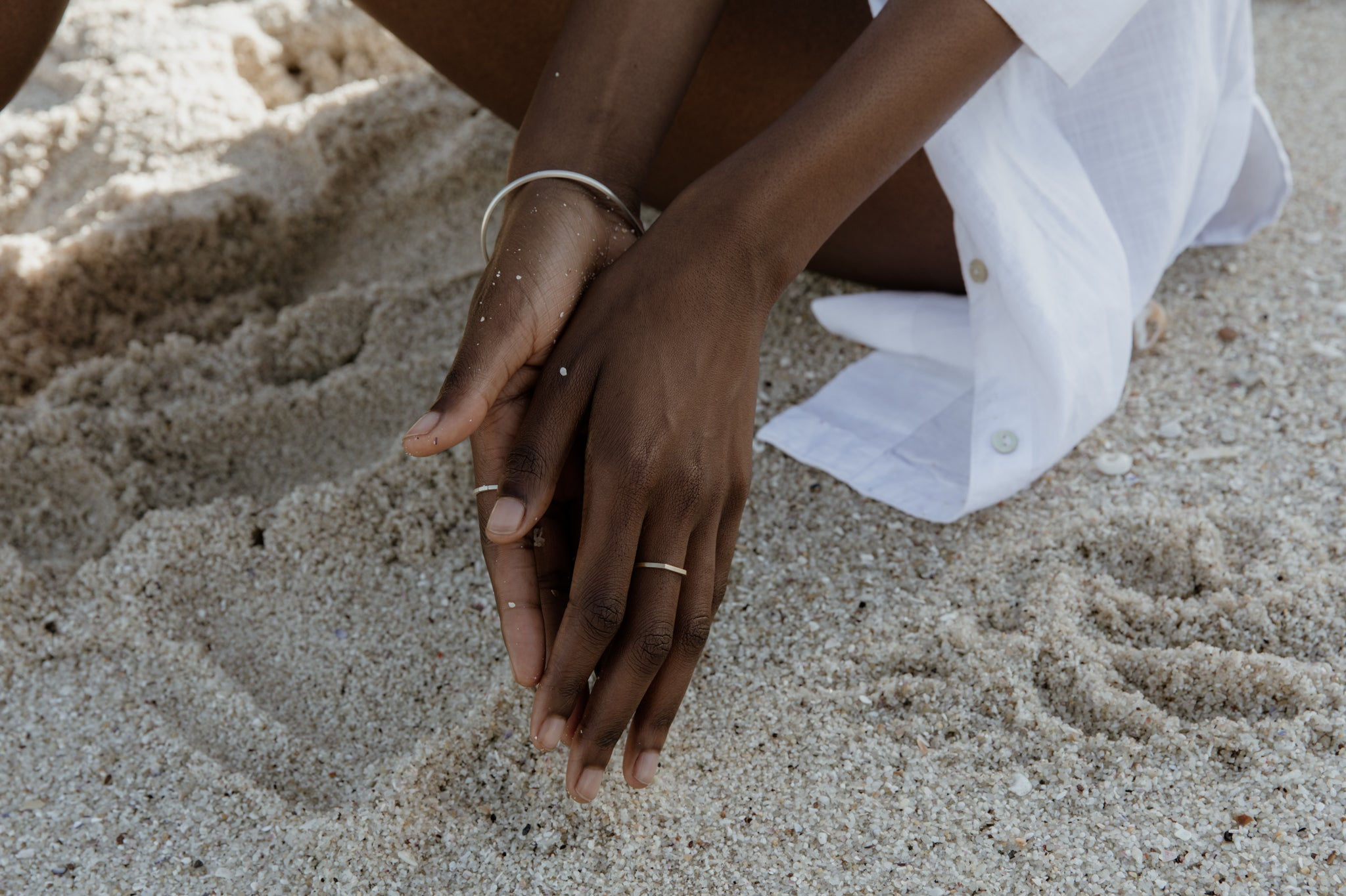 Calm ocean and woman wearing recycled silver bangle and fairtrade eco-friendly recycled gold ring