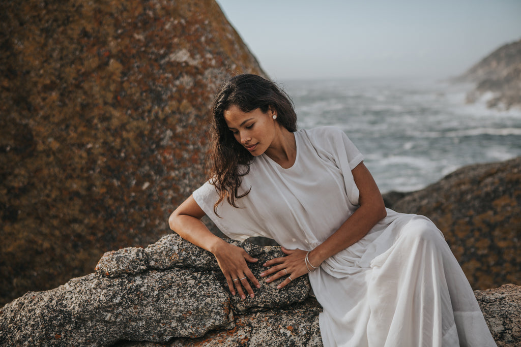 Quite reflections, woman relaxing on rocks next to the ocean wearing ethical, slowfashion fashion outfit and recycled silver jewelry