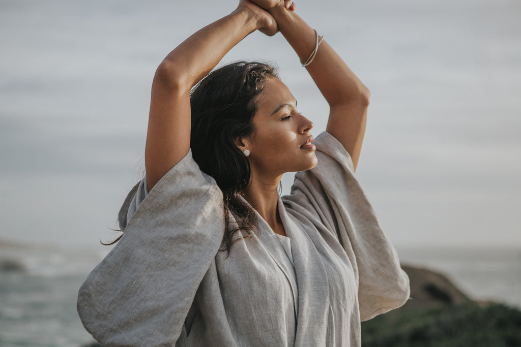 A clam moment at the beach weraing a linen wrap dress and recycled silver minimalist earrings and bangles
