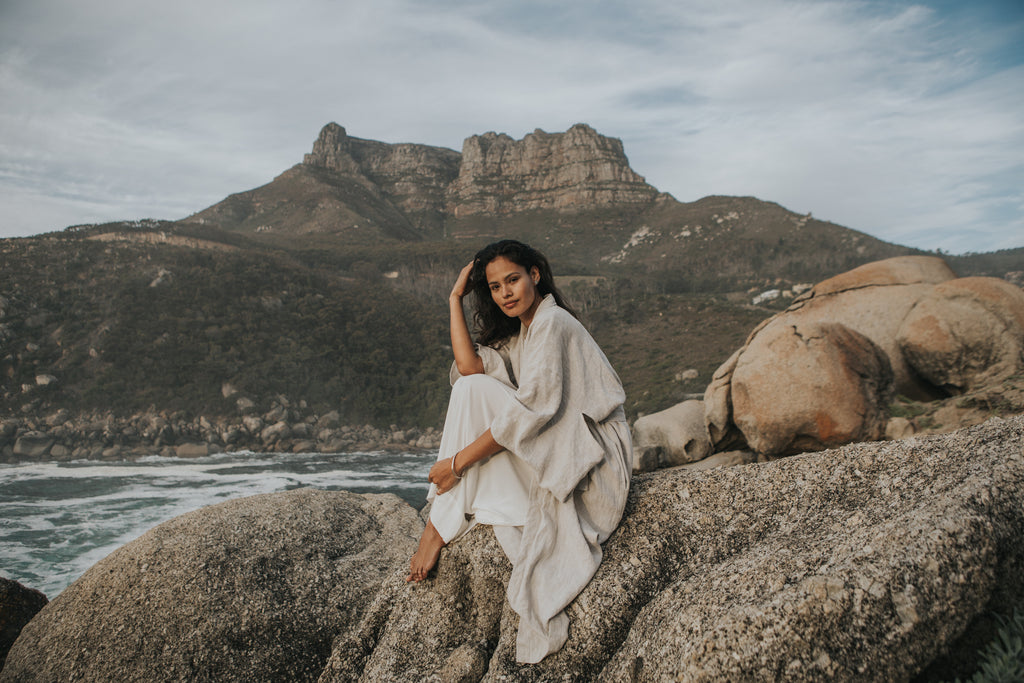 My soul lives in the ocean, woman sitting at the base of Table Mountain wearing a slowfashion linen dress and eco-friendly, ethical silver jewellery