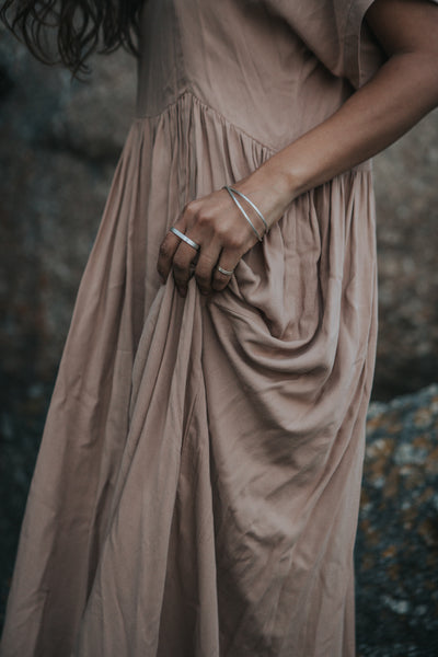 Woman wearing recycled silver handmade Double Finger Ring and linen dress