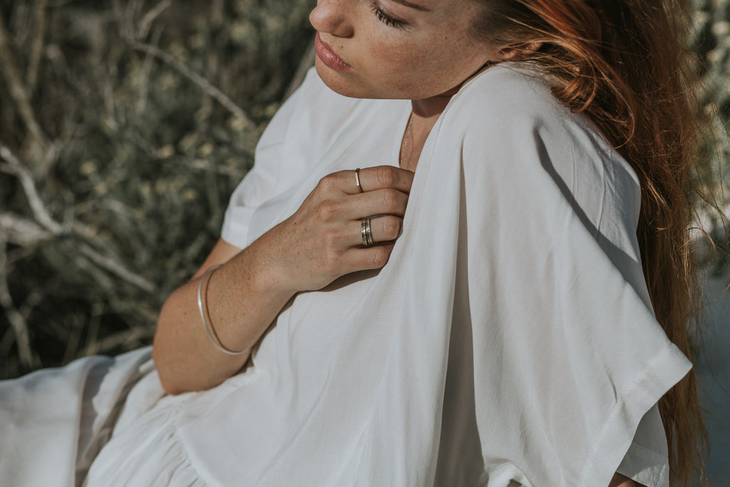 Woman in white slowfashion dress wearing sustainable silver and gold jewellery in the dunes