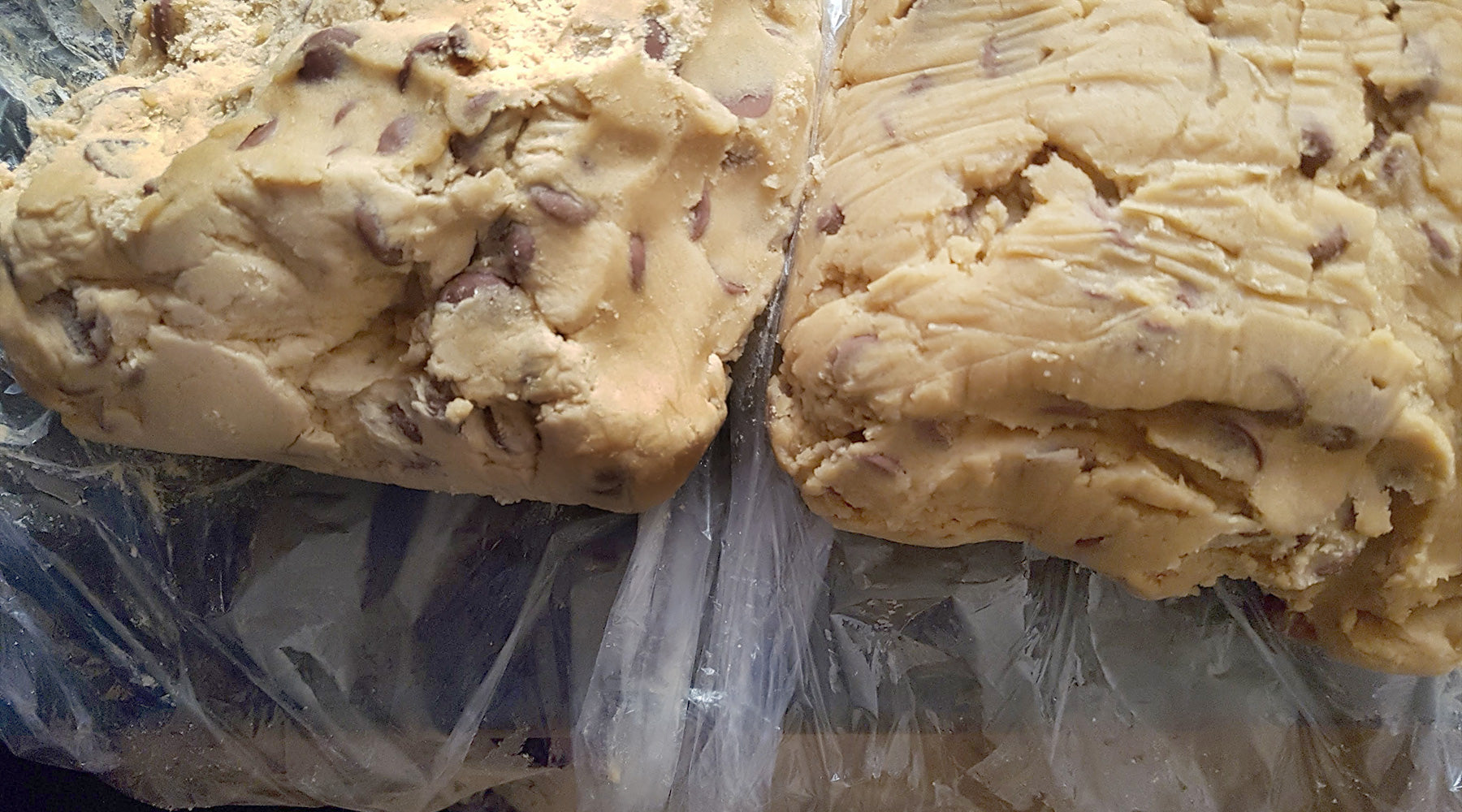 Two batches of chocolate chip cookie dough wrapped in plastic