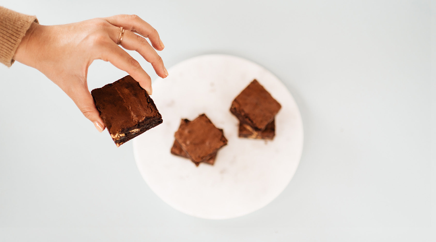 Hand holding brownies above a plate of brownies
