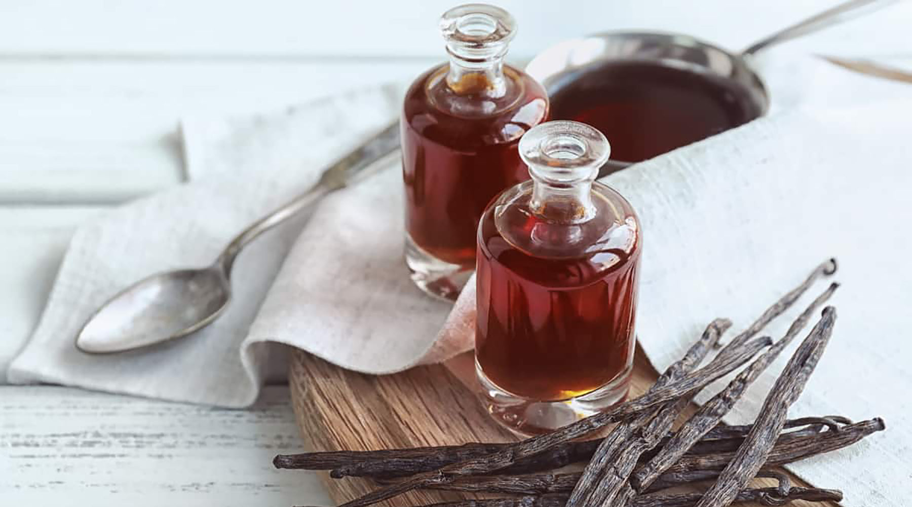 Vanilla extract in a bottle next to vanilla beans