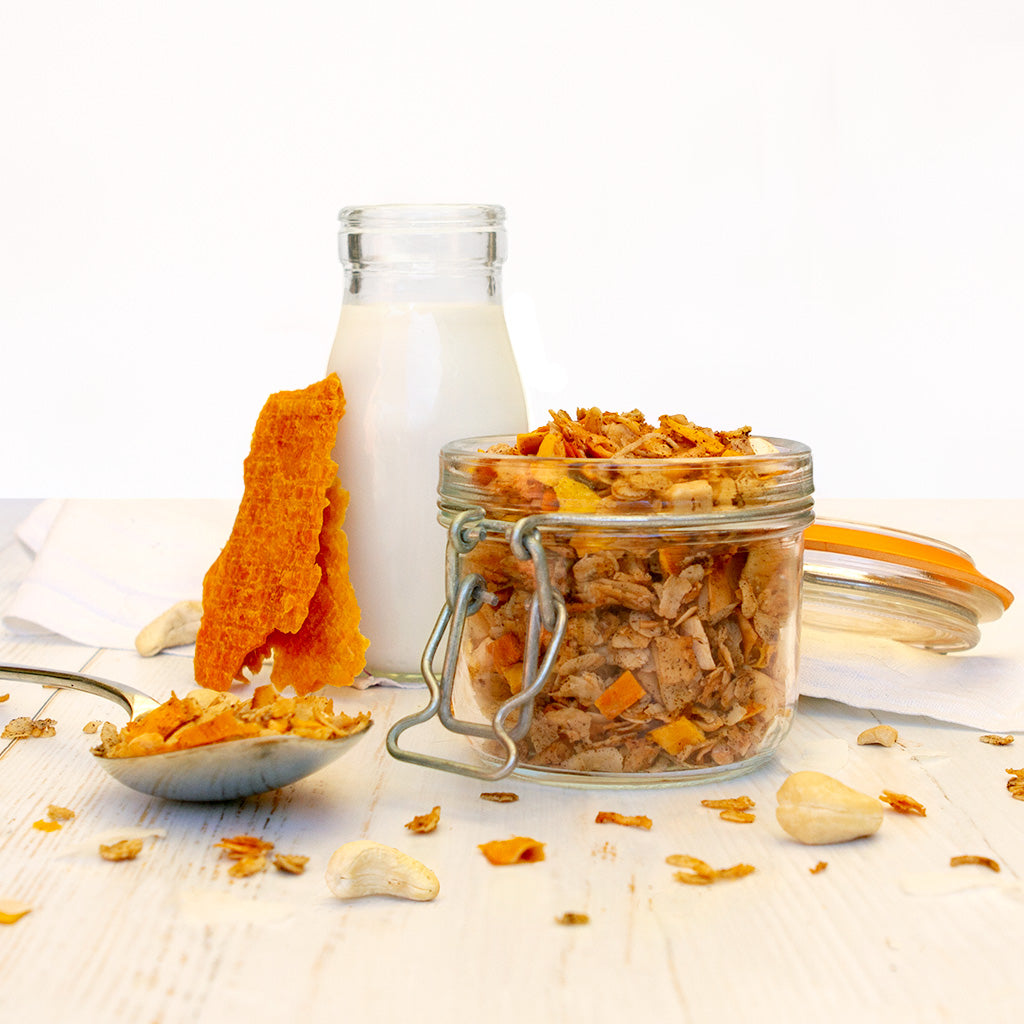 Dried Mango, Cashew and Coconut Granola in a clip top jar sitting in front of a bottle of milk