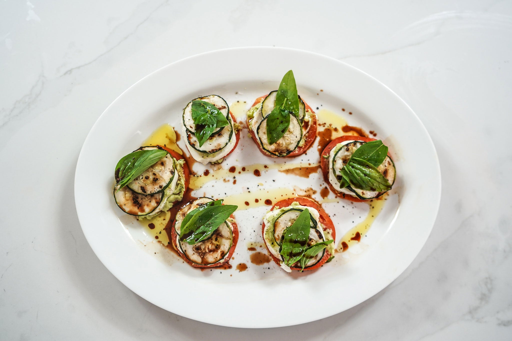 Grilled zucchini mozzarella tomato stacks with fava bean spread