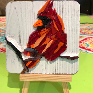 Red mosaic glass cardinal sitting on a snow covered branch shown with easel