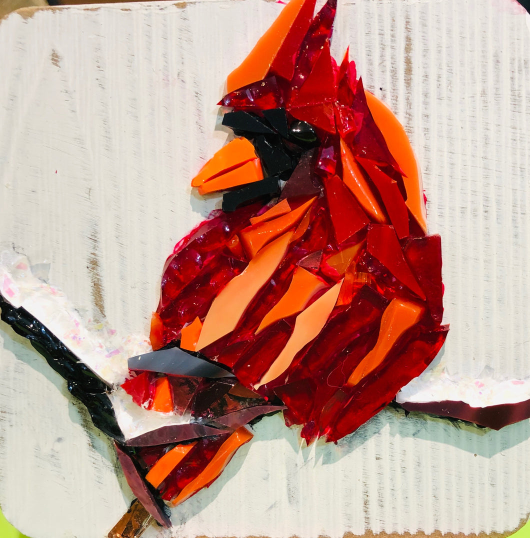 Red mosaic glass cardinal sitting on a snow covered branch