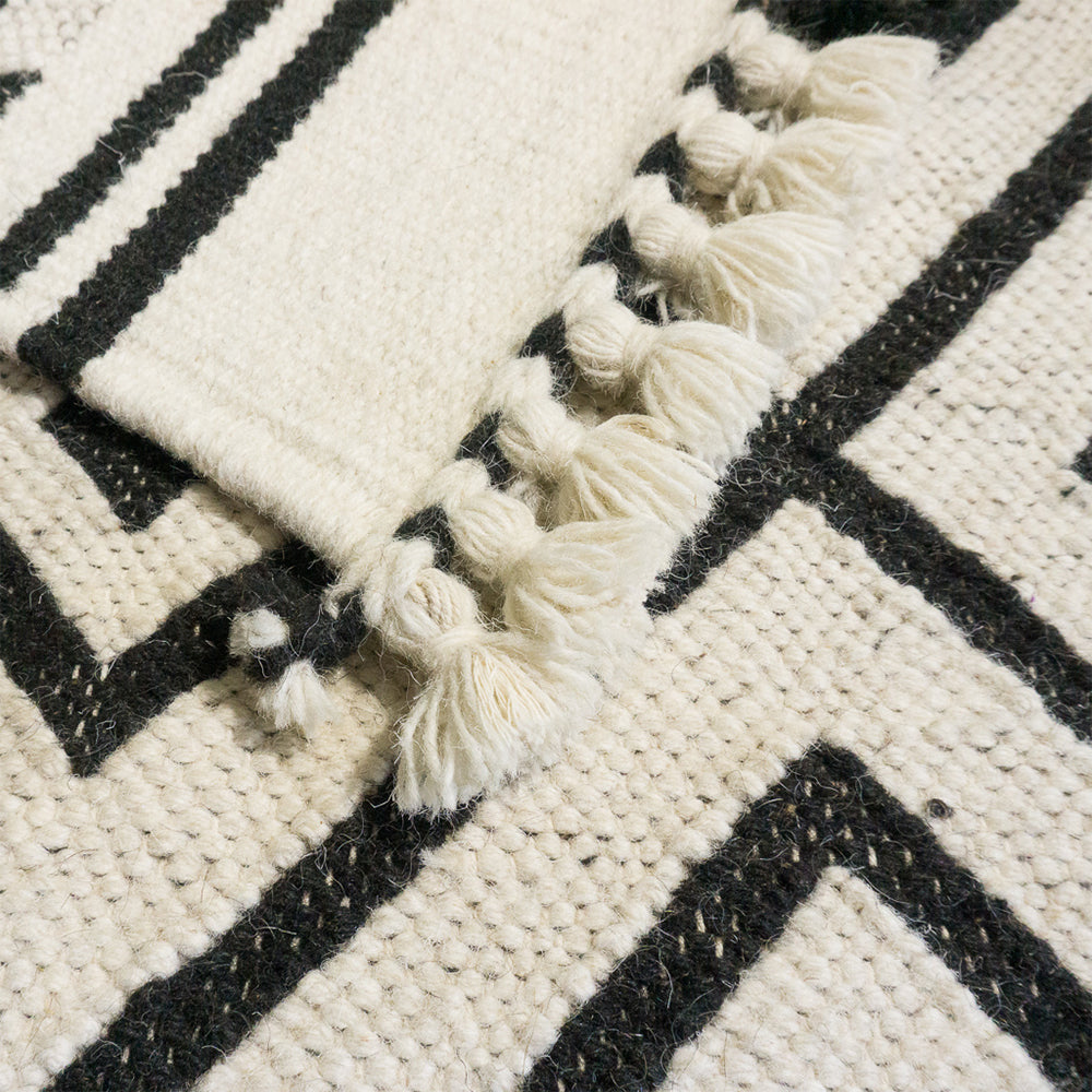 Tapis vu de près. Tapis coloré à rayures, en coton et en laine de mouton. Tapis éthique et équitable tissé à la main par des artisans en Inde. Rectangle - rectangleboutique.com