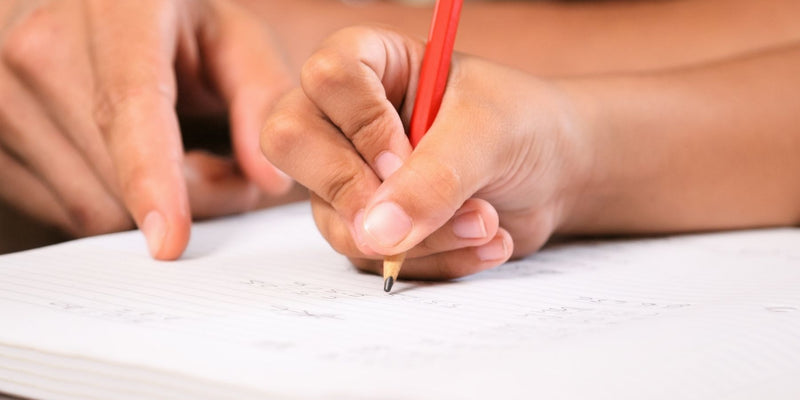 Child writing in a book with a pencil
