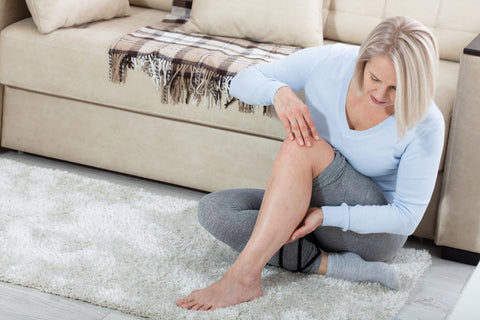 Middle-aged woman examining leg.