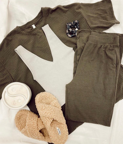 a flatlay of a green loungewear outfit with pink slippers and a white tank top