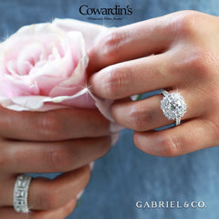 a person wearing a large diamond ring holds a pink rose