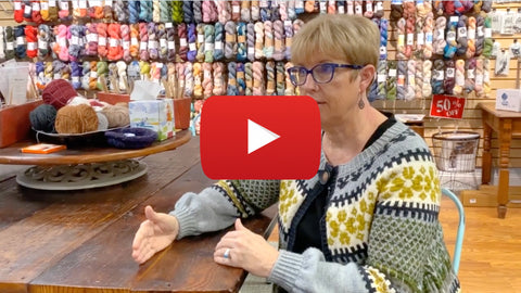 Woman in wool shop with play button