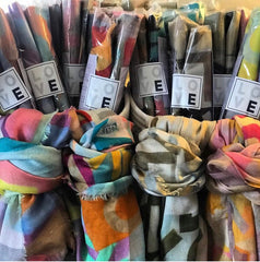 a collection of colorful scarves are lined up