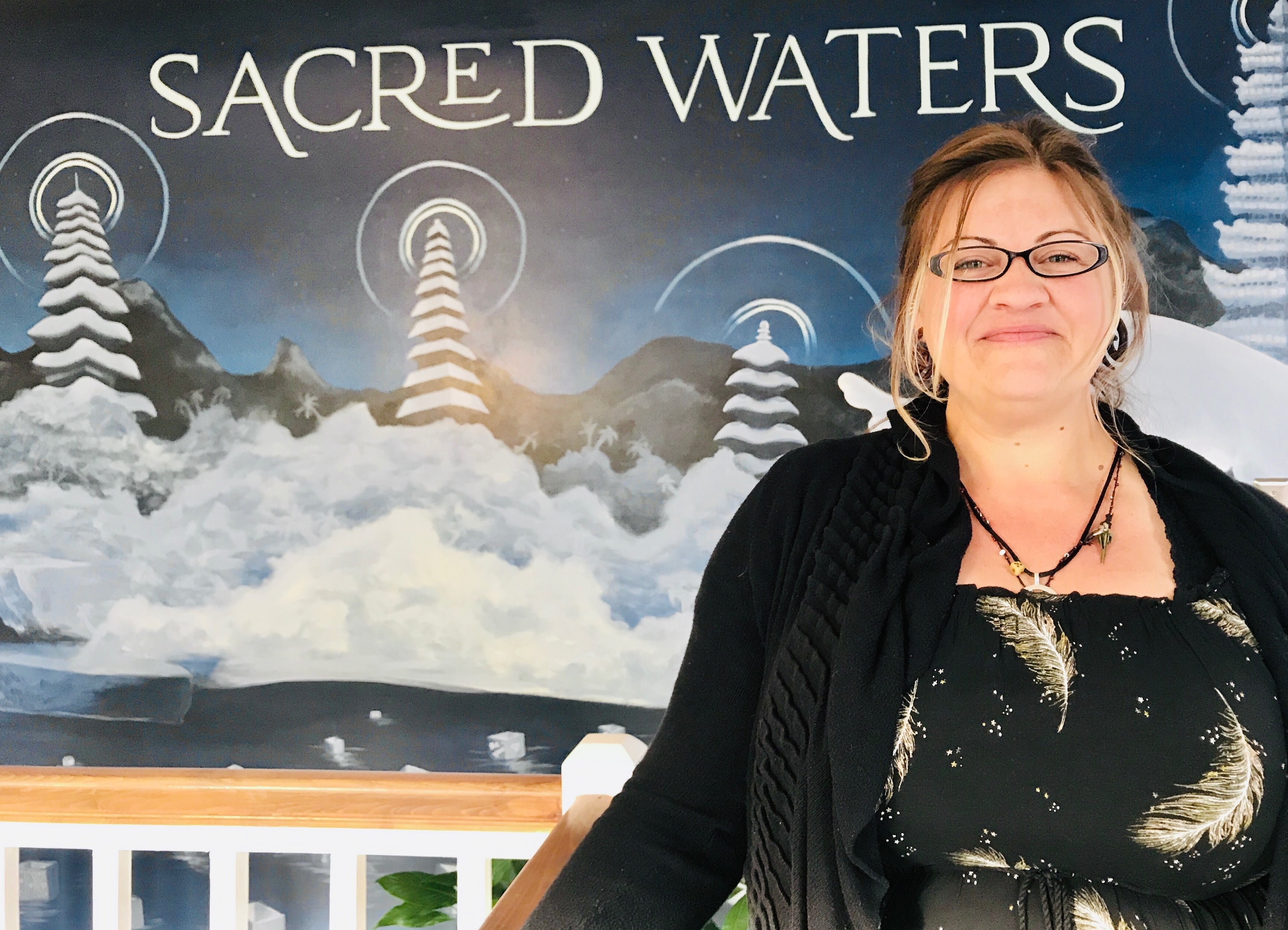 Camille stands in front of a wall with Sacred Waters logo on it