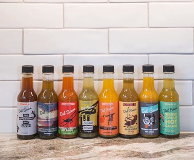 a lineup of hot sauces on a counter