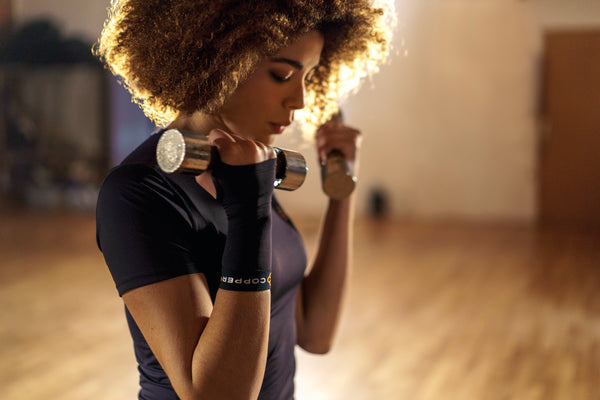 Young woman wearing copper compression sleeves lifts silver dumbbells