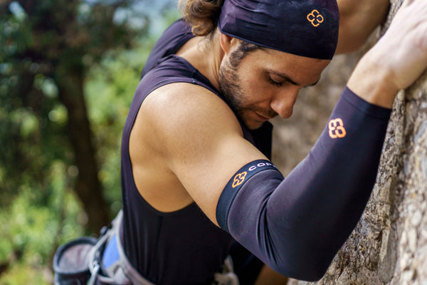 Athletic Man wears copper compression sleeve and head band while rock climbing