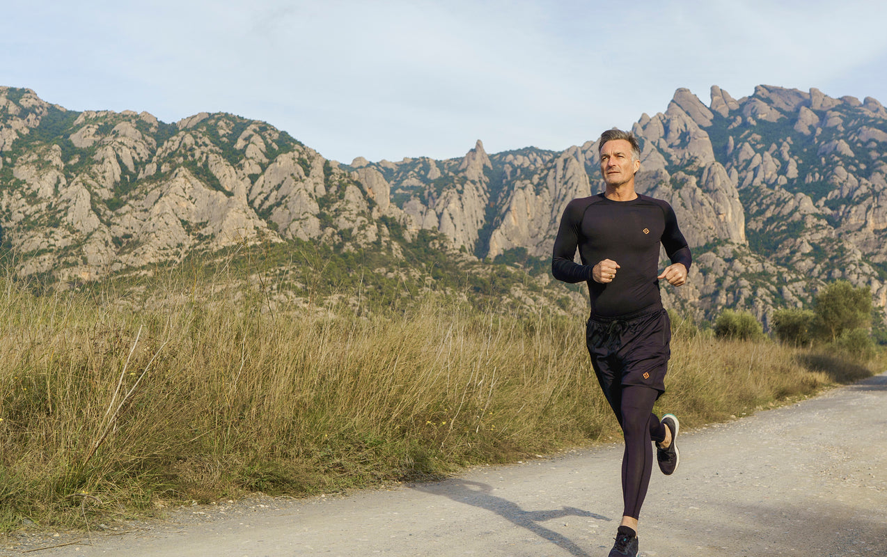 Middle aged man wearing copper compression active wear confidently runs with a mountain back drop