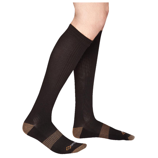 Someone standing in front of a white background wearing black and grey copper compression knee socks
